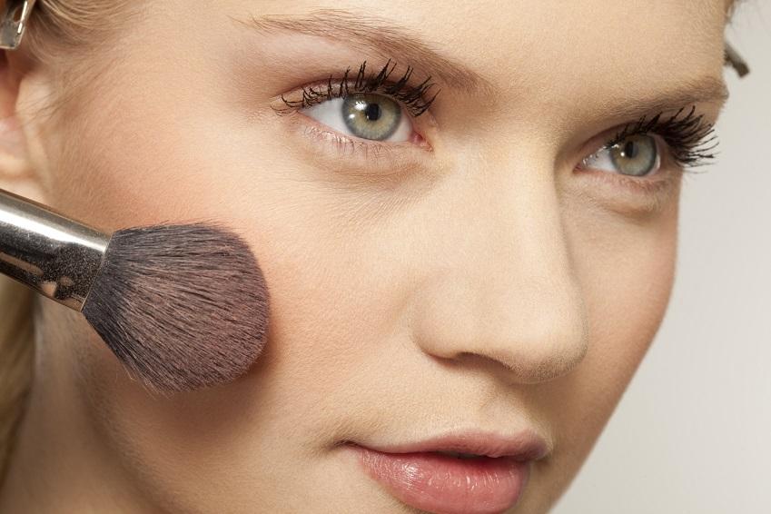 Junge Frau trägt Make-Up auf