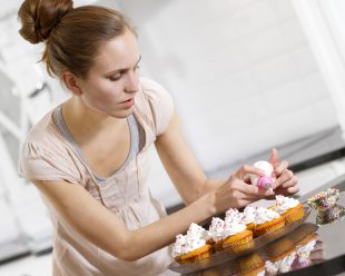 A woman baking muffins or cupcakes in white kitchen.